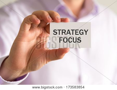 Businessman Holding A Card With Strategy Focus Message