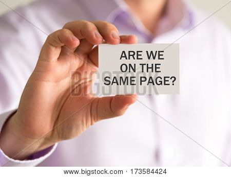 Businessman Holding A Card With Are We On The Same Page ? Message