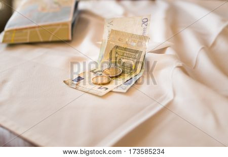 Twenty-five euro banknotes and two coins of one payment Deposit accounts cafe shop on a table with white tablecloth trip to Europe