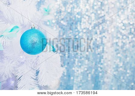 Blue Christmas toy hanging on a white spruce with snow. New Year background. Christmas concept
