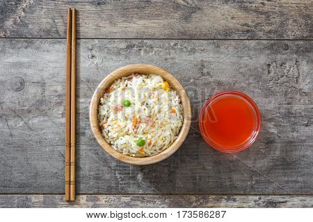Fried chinese rice with vegetables on wooden background
