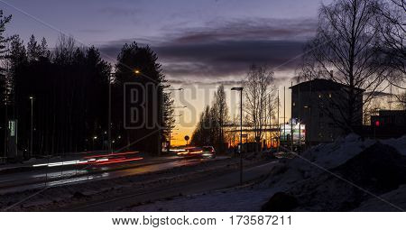 UMEA, SWEDEN ON FEBRUARY 14. View of a street, traffic, buildings, neon sign in nightfall, sunset on February 14, 2017 in Umea, Sweden. Hill in silhouette. Editorial use.