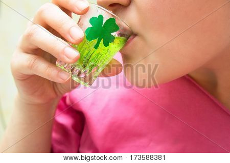 woman drinks an alcoholic shot on St. Patrick's day