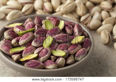 Bowl with unshelled pistachio nuts and shelled ones on the background