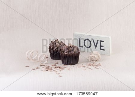 Two chocolate cupcakes with chocolate sprinkles and a love sign