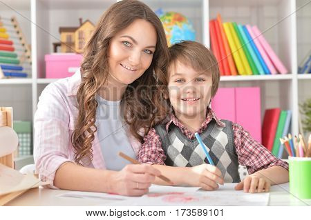 Mather and her little son drawing with colorful pencils