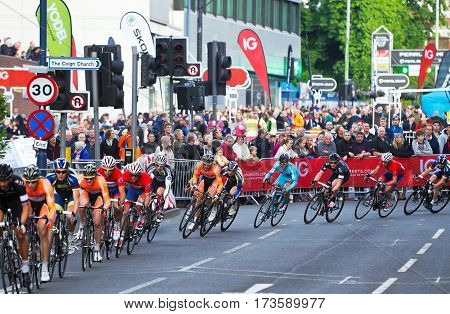 WOKING, UK - JUNE 11: Unnamed riders competing in the Pearl Izumi road race series head around the first major corner onto a main thoroughfare at the Woking Town circuit on June 11, 2013 in Woking
