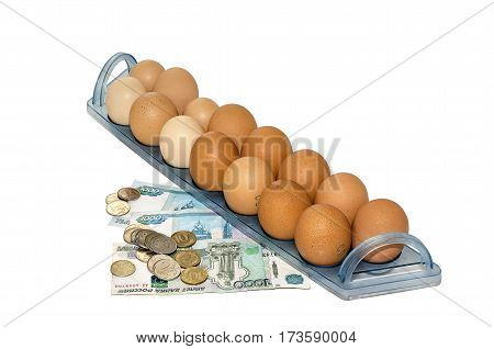 Tray of chicken eggs and money on a white background closeup