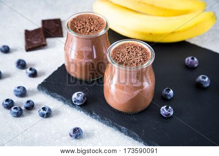 Chocolate Banana Smoothie With Chia Seeds And Blueberry On A Slate And Stone Background.