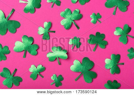 Green paper clovers patterned over pink background, top view