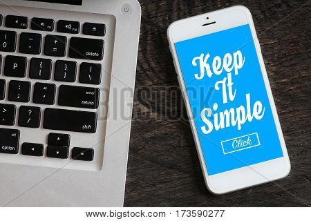 """Keep It Simple"" words on smartphone with a laptop near it - website multimedia and business concept"