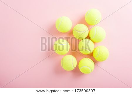 Tennis balls over pink background, top view