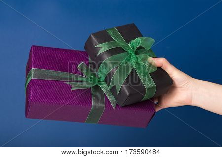 Three wrapped gift boxes in a hand over blue background