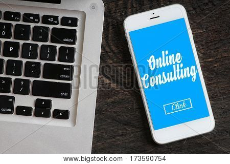 """""""Online Consulting"""" words on smartphone with a laptop near it - website multimedia and business concept"""
