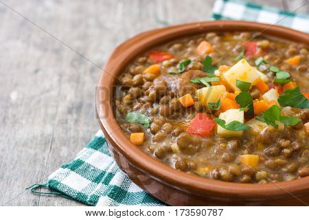 Lentil soup in a bowl on wooden background
