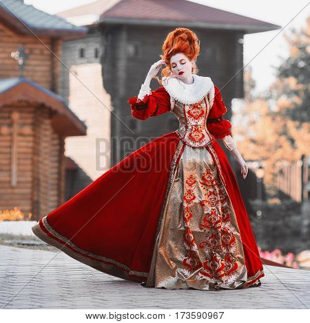 Red Queen in the castle. Red-haired woman in a chic vintage dress. Fashion Photo of queen. Redhead woman in red dress
