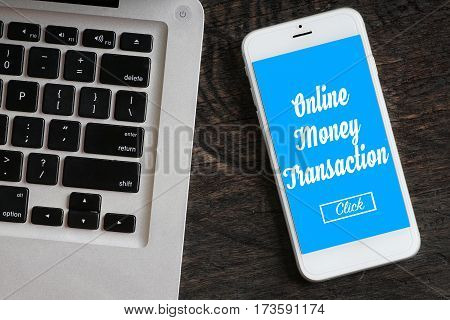 """""""Online Money Transaction"""" words on smartphone with a laptop near it - website multimedia and business concept"""