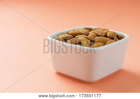 Almonds nuts in white bowl on coral pink background. Healthy lunchbox snack horizontal
