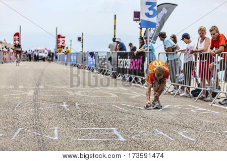 Mont Ventoux France- July 14 2013: A boy paiting the road to Mont Ventoux while amateur cyclists climb few hours bevore the apparition of the cyclists during the stage 15 of the 100 edition of Le Tour de France 2013.