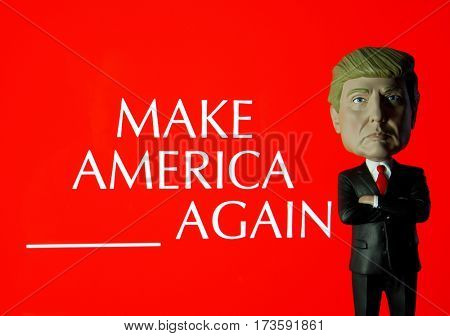 Donald Trump Bobble Head figure standing in front of sign reading Make America BLANK again
