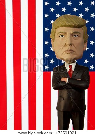 Donald Trump Bobble Head figure standing in front of an American Flag