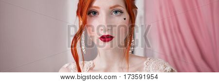 red-haired girl in a wedding dress bright unusual appearance red nails a girl with pale skin beautiful wedding dress a heart on her cheek bright make-up on a white background fetish model