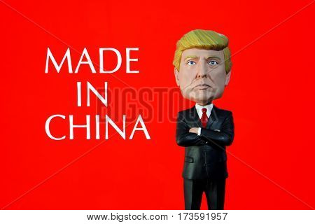Donald Trump Bobble Head figure standing in front of sign reading Made in China. Many of Trump's clothing line are made overseas