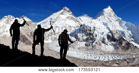 View of mount Everest and Lhotse from Pumo Ri base camp and silhouette of group of climbers with ice axe in hand Everest area Khumbu valley Sagarmatha national park Nepal