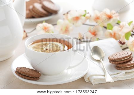 Cup of lemon tea on white background