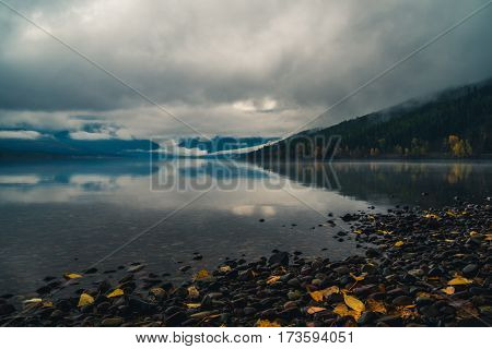 Clouds and mountains reflected in a calm lake.