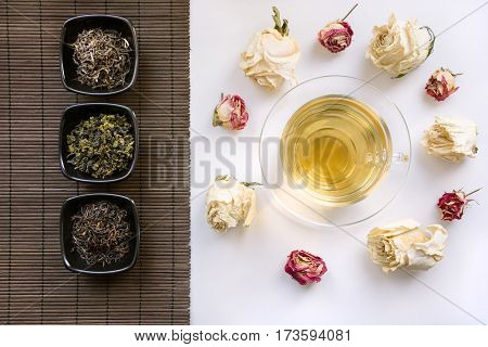 Glass cup of green tea with dry roses around and mat with different kinds of green tea. China's concept.