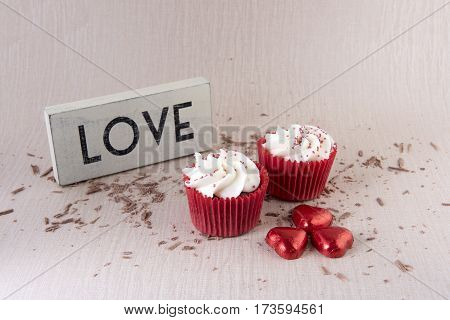 Two red velvet cupcakes with chocolate, hearts and a love sign