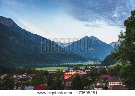 View of the Alpine village Elbigenalp, Austria nestling in a forested valley surrounded by high mountain peaks and a popular tourist destination for winter sport