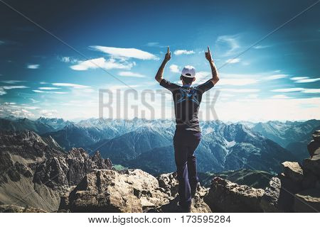 Mountaineer celebrating reaching the summit of a high rocky alpine peak standing with his arms raised looking out over a vista of mountain ranges and rugged alps in Austria