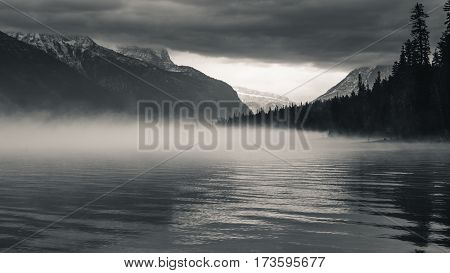 Black and white image of a foggy forest lake