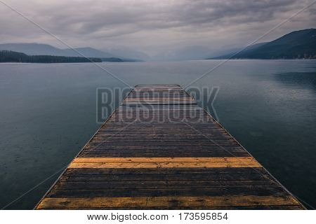 Image of a dock overlooking a calm overcast lake.