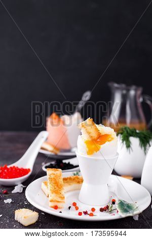The soft-boiled egg in an eggcup with toasted bread on a dark stone background