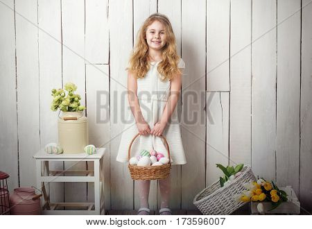 Little blonde girl holding basket with painted eggs. Easter day