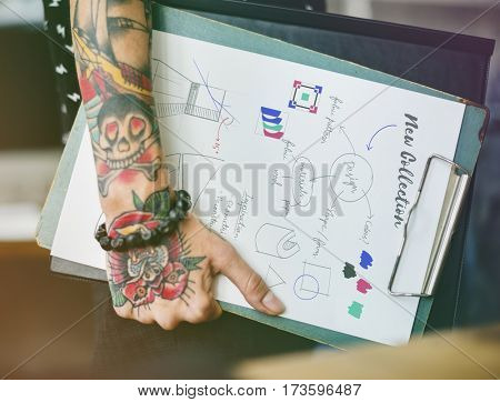 Fashion designer holding clipboard of dress pattern