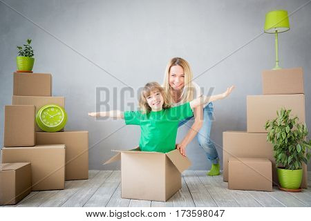 Happy family playing into new home. Mother and child having fun together. Moving house day and express delivery concept