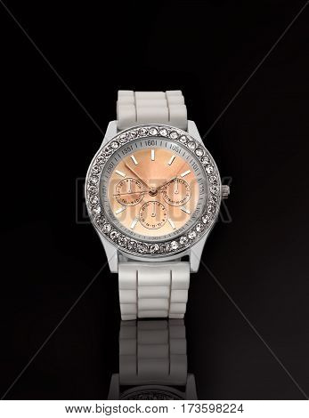 Women's wristwatch with a white strap. On a black background