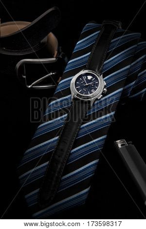 Men's wrist watch on a black strap in the set with a tie and a lighter. On a black background