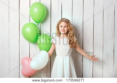 Cheerful little blonde girl with balloons on white wood background.