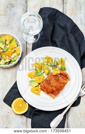 Honey soy baked cod with avocado orange salsa on a wood background.