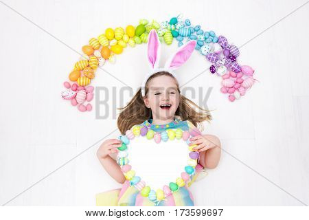 Funny little girl with bunny ears having fun on Easter egg hunt. Child playing with colorful Easter eggs. Kids play with pastel color rainbow eggs. Spring and Easter art and crafts for children.