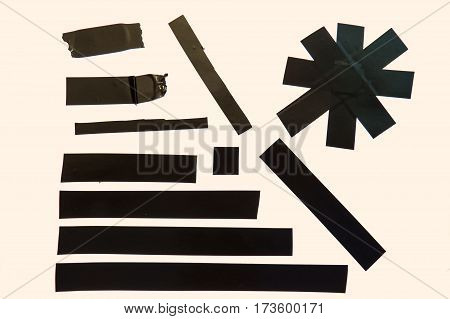 A collection of used black adhesive tape pieces