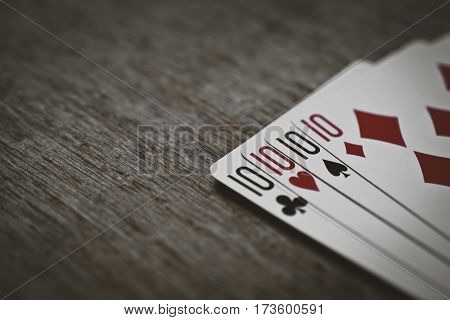 four tens on a wooden table. concept of gambling and place for your text