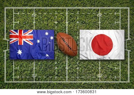 Australia vs. Japan flags on green rugby field, 3 D illustration