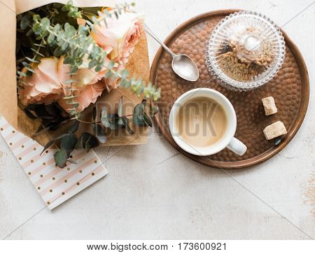 Feminine tabletop, home office with flowers, coffee and notepad on white textured background