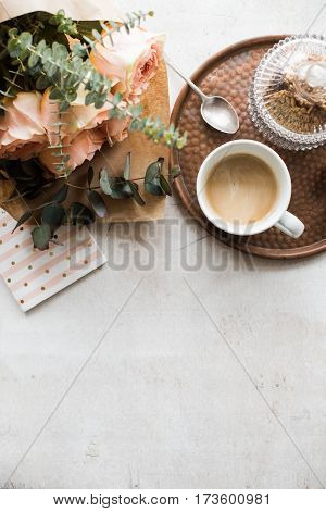 Feminine tabletop, home office with flowers, coffee and notepad on white textured background, copy space